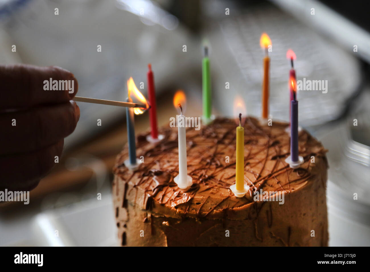 Lighting candles on chocolate birthday cake in office - Stock Image