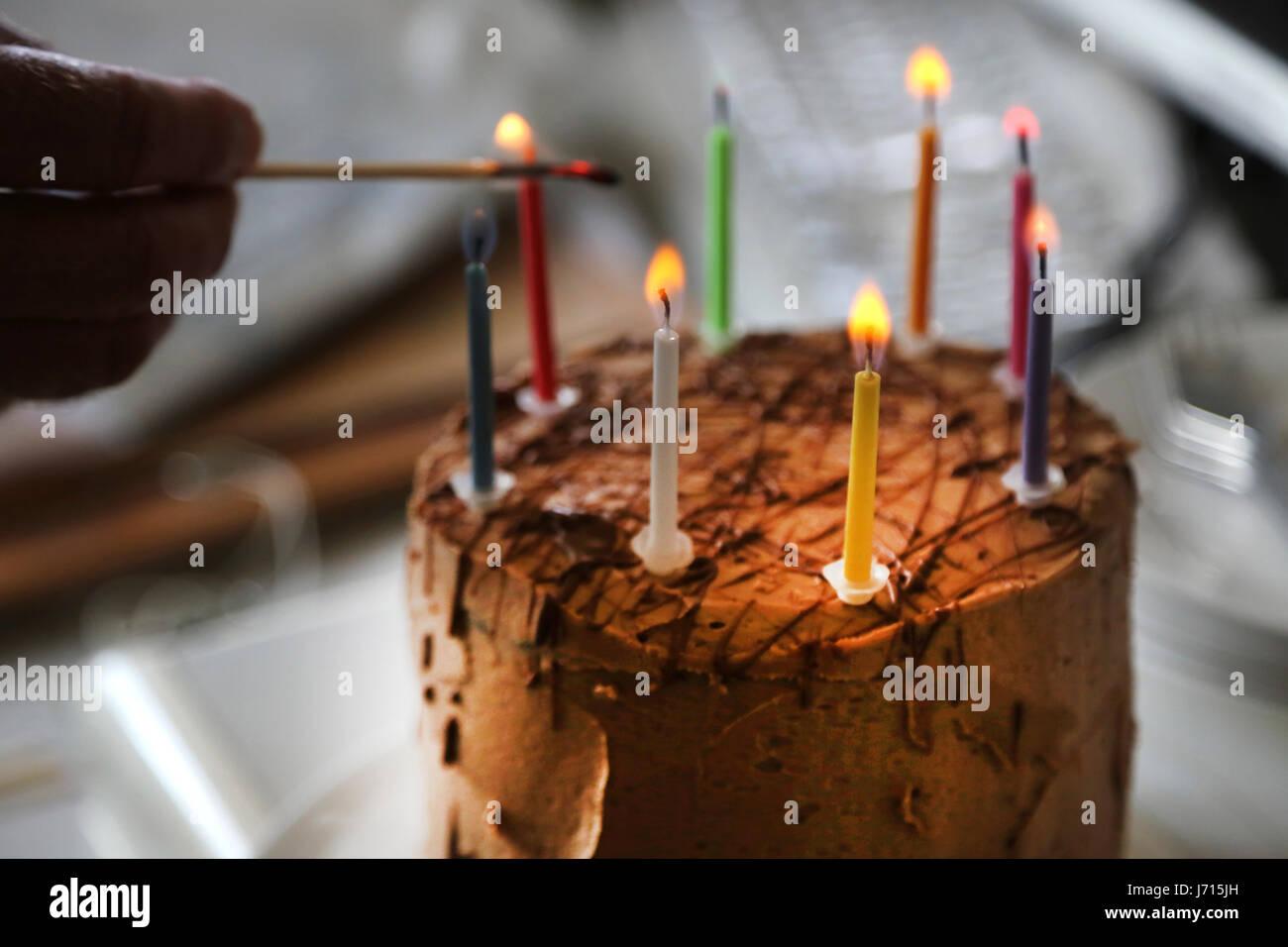 Lighting candles on chocolate birthday cake - Stock Image