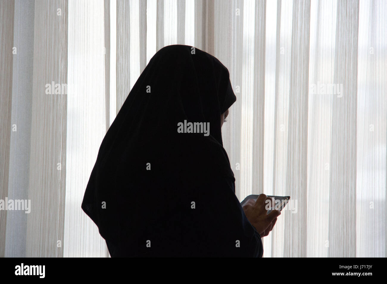 Woman in hijab playing with iPad in a restaurant, Yazd, Iran - Stock Image