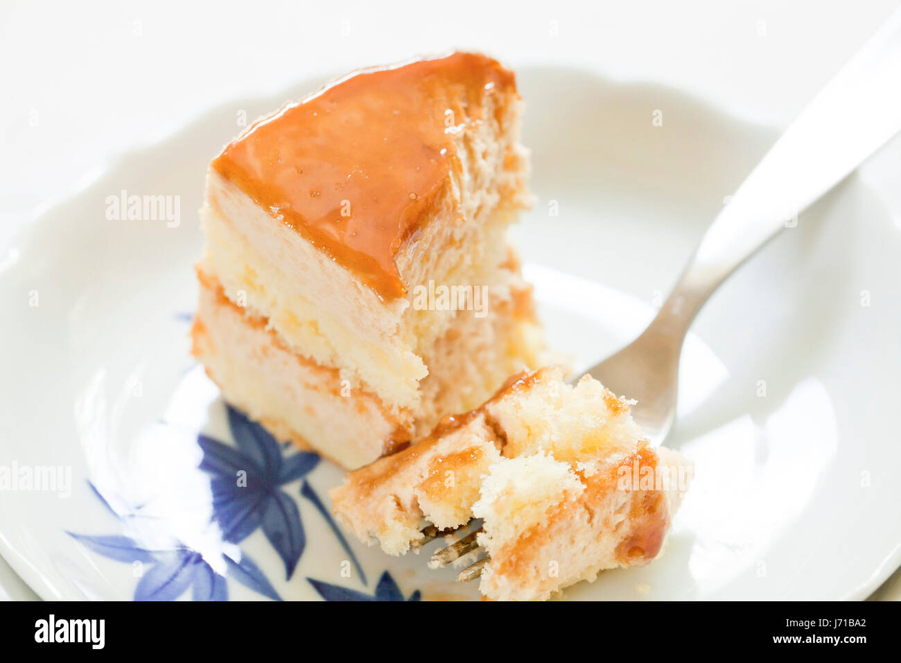 Half-eaten slice of layered cheesecake on dish - USA - Stock Image