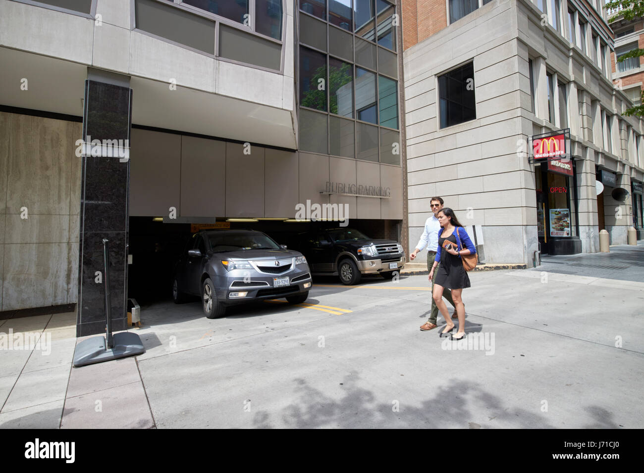 couple walking past car coming out of underground and multi storey parkade parking garage downtown Washington DC USA Stock Photo