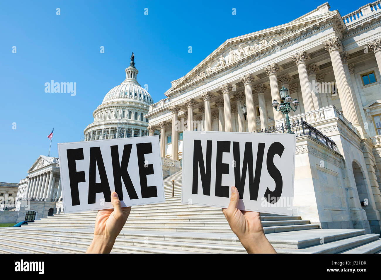 Hands holding signs protesting fake news coverage in front of the Capitol Building in Washington DC, USA - Stock Image