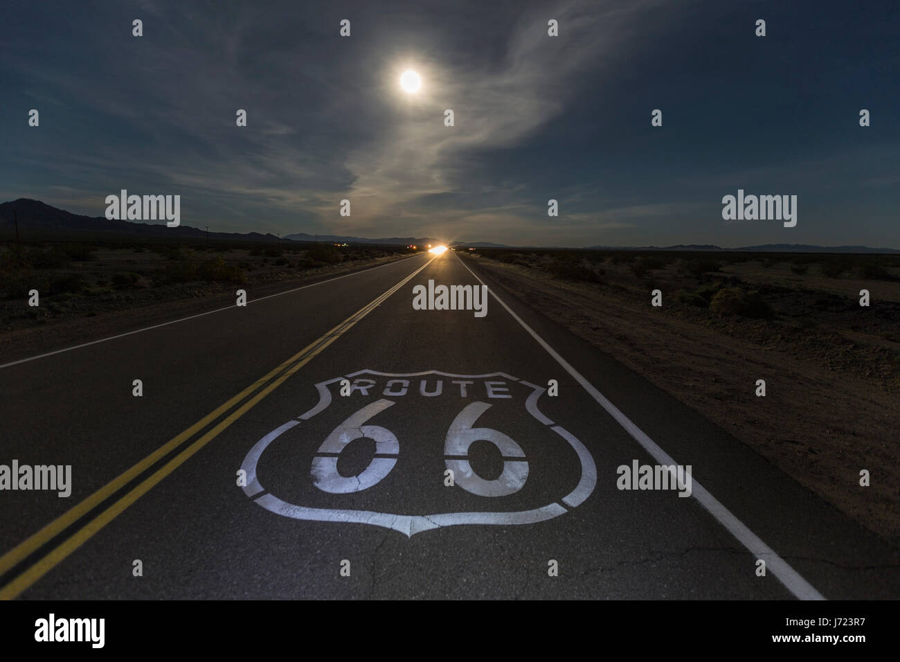 Route 66 sign with full moon and oncoming headlights in the California Mojave desert. - Stock Image