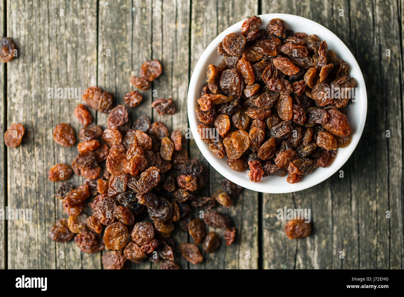 Sweet dried raisins in bowl. Top view. - Stock Image
