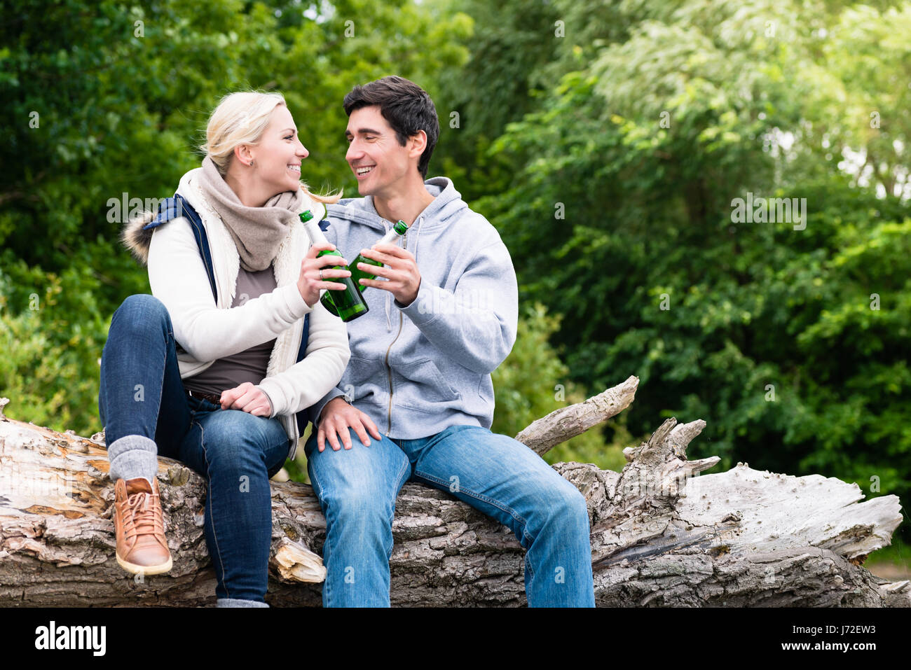 Lovers in vacation sitting at waterside clinking beer bottles - Stock Image
