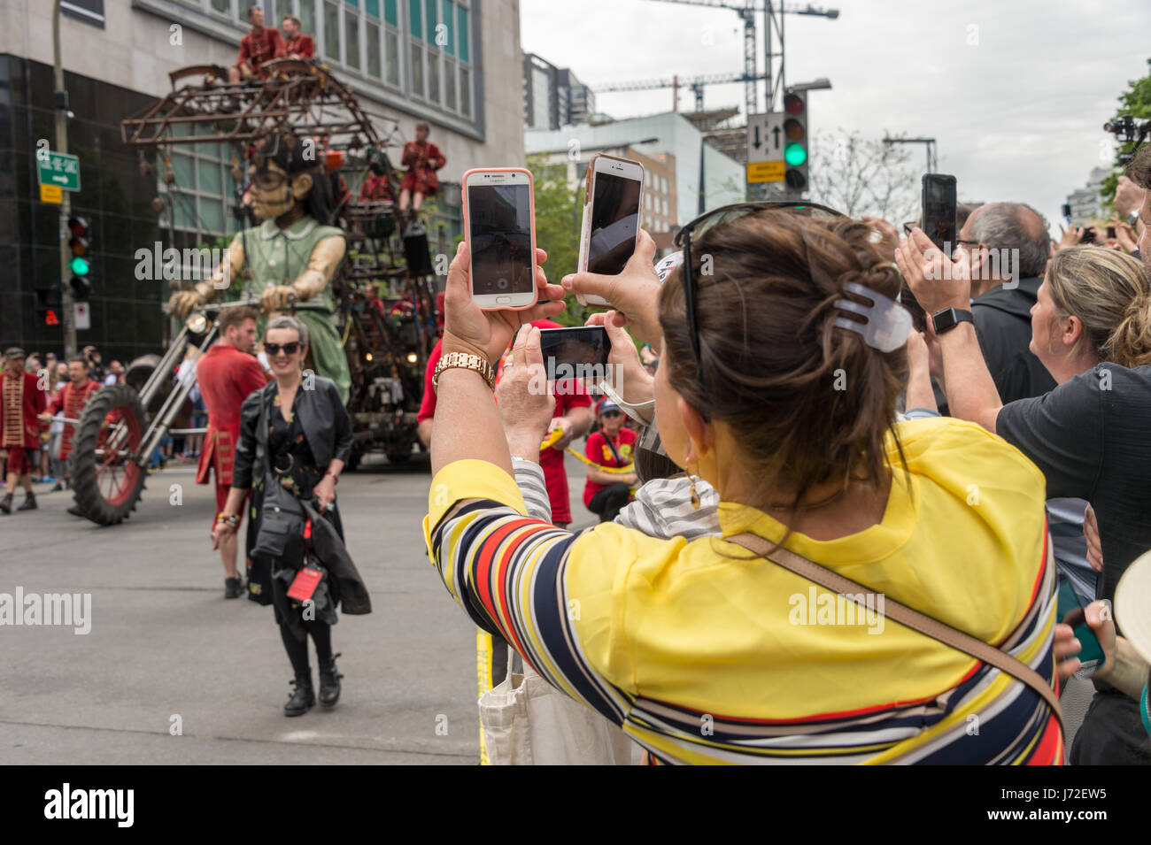 Montreal, CA - 21 May 2017: Woman filming Royal de Luxe Giants show with two cellphones - Stock Image