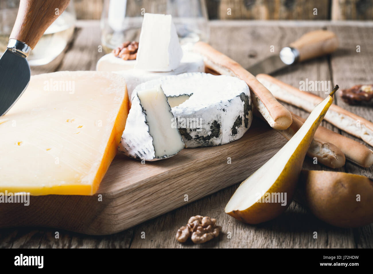 Cheese platter served with white wine, jam and walnuts on wooden board on rustic table - Stock Image