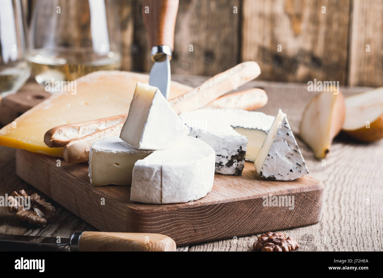 Cheese platter served with white wine,pear and walnuts on wooden board on rustic table - Stock Image