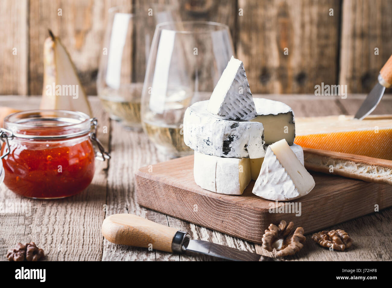 Cheese platter served with white wine, jam and walnuts on wooden board on rustic table Stock Photo
