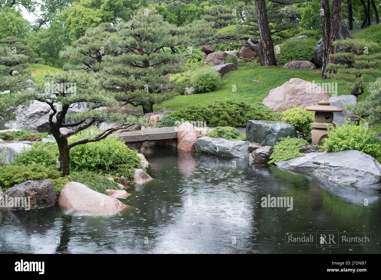 A Stone Lantern Near Bridge That Crosses Pond In Japanese Garden