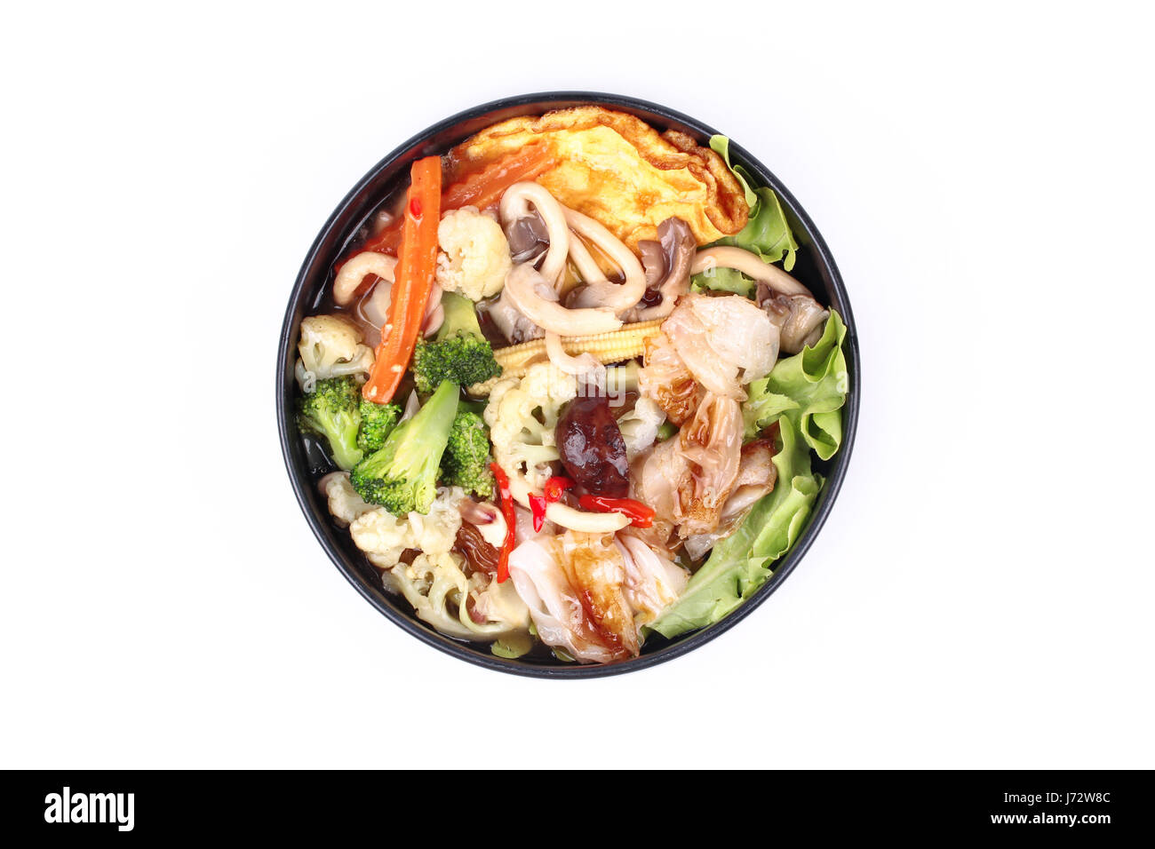 Thai Chinese food,Fried big noodle with omelet topped mixed vegetable in soup as carrot,corn,cauliflower,green oak,broccoli,mushroom - Stock Image