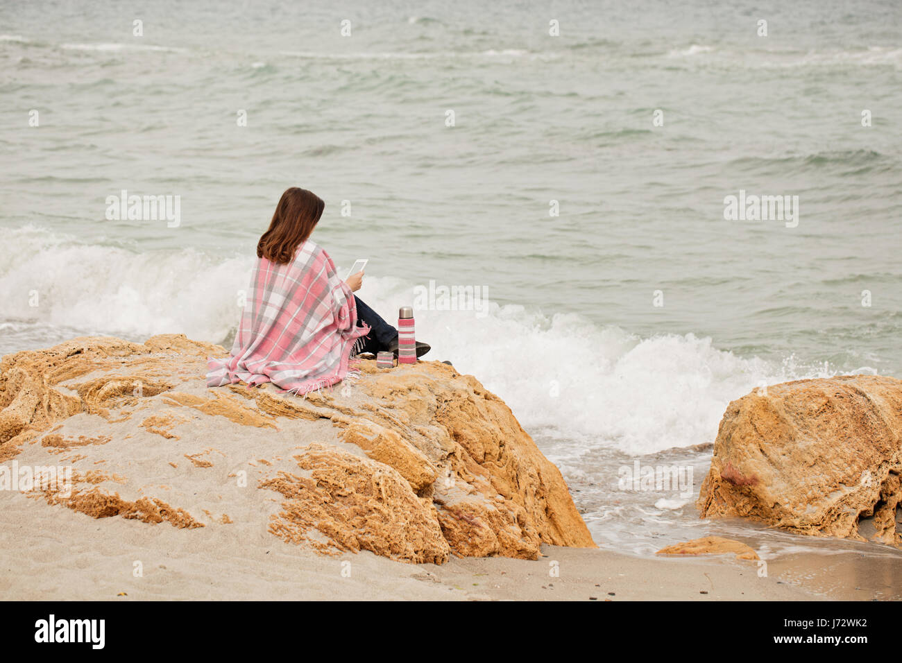 Young woman is covered with a rug sits on the seashore and reads an ebook. Selective focus. - Stock Image