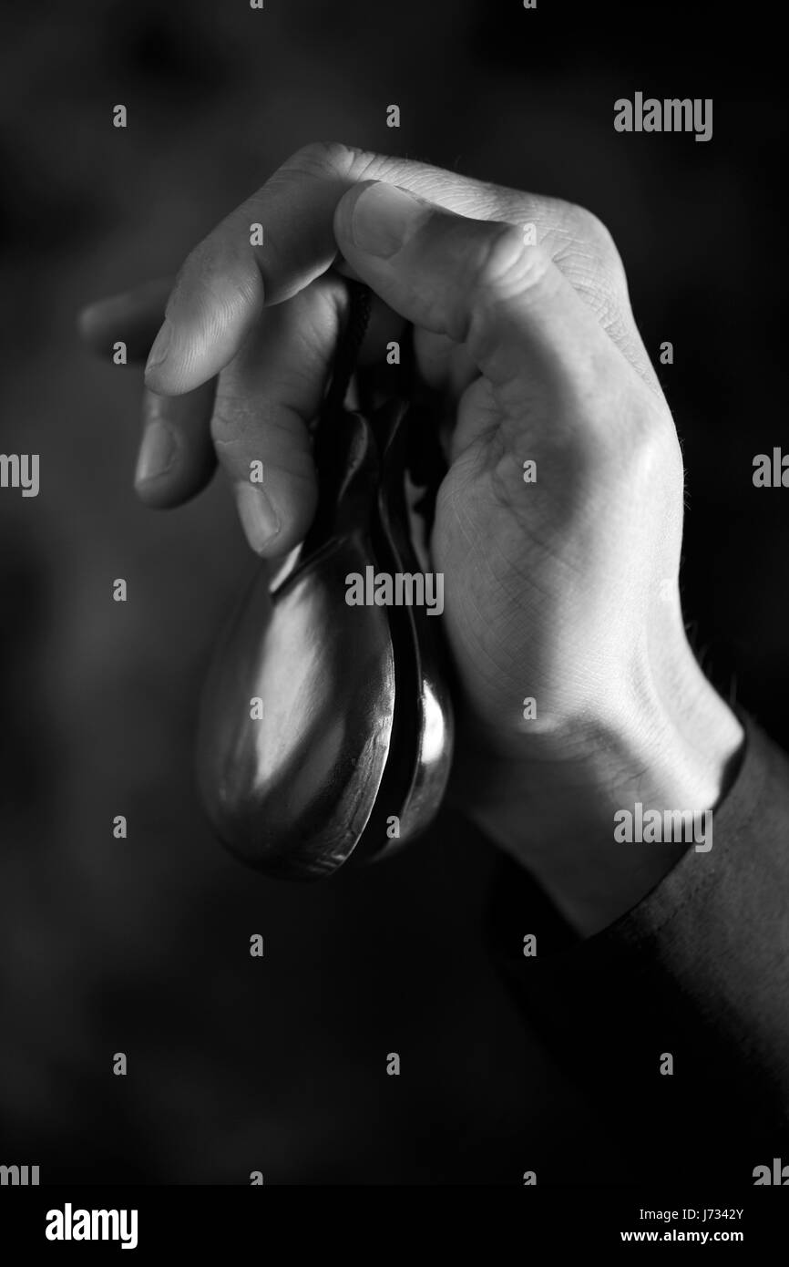 closeup of the hand of a young caucasian man playing the castanets against a dark background, in black and white - Stock Image