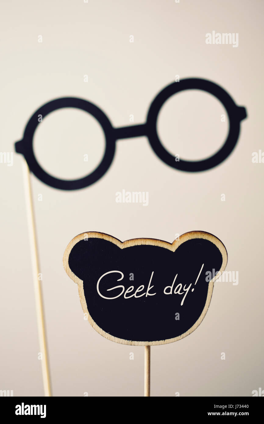 a pair of round-framed eyeglasses attached to a wooden handle and the text geek day written in a black signboard, - Stock Image