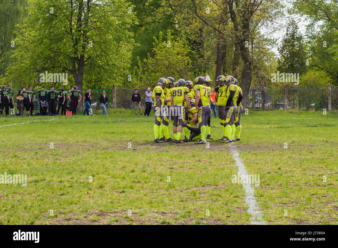 Players in a Huddle During American Football Match - Stock Image