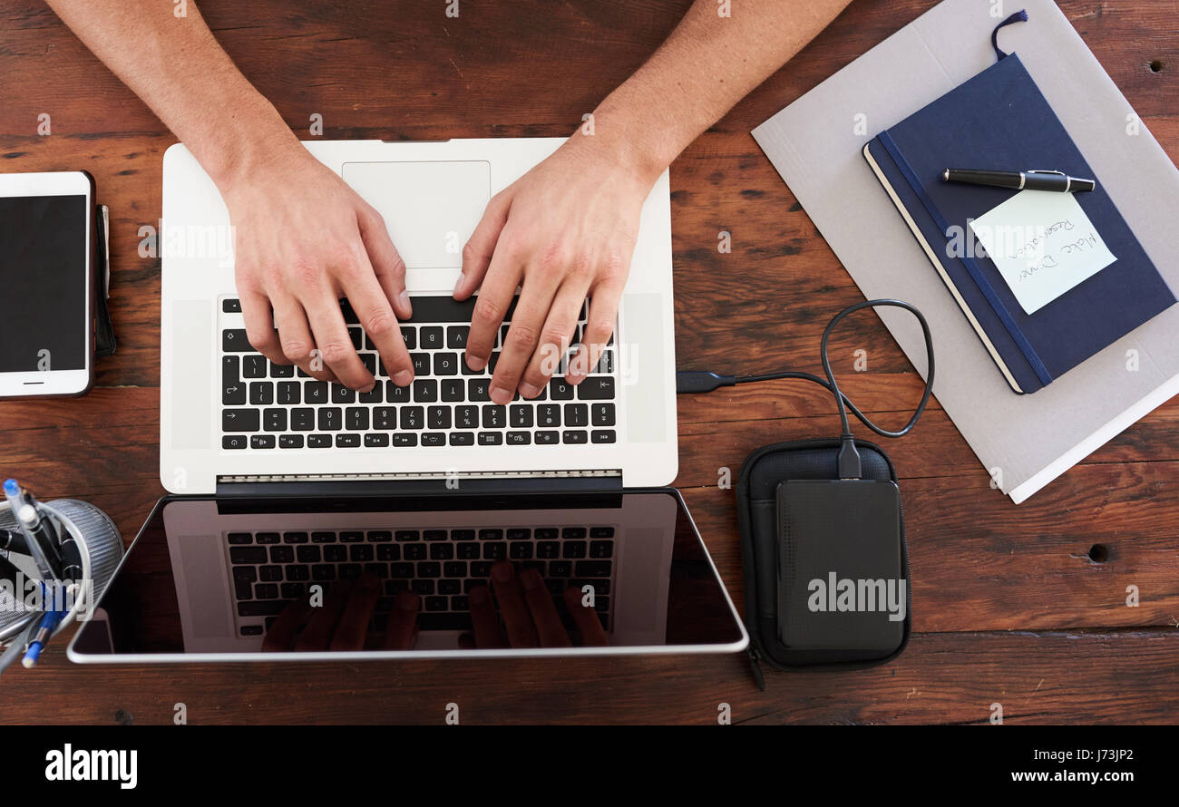 Overhead view of caucasian hands typing on a modern laptop Stock Photo