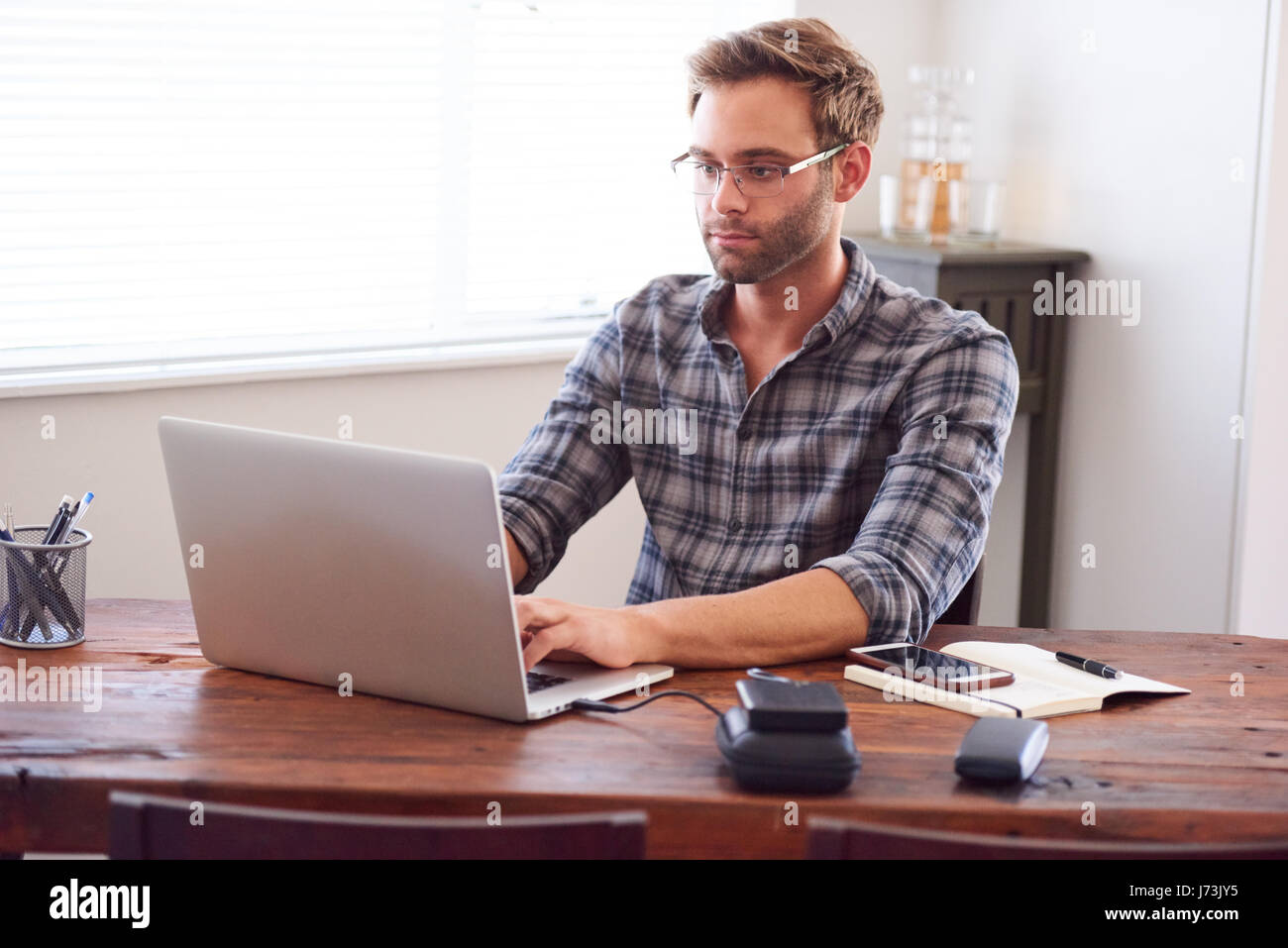 Modern man typing on a laptop while seated at desk Stock Photo