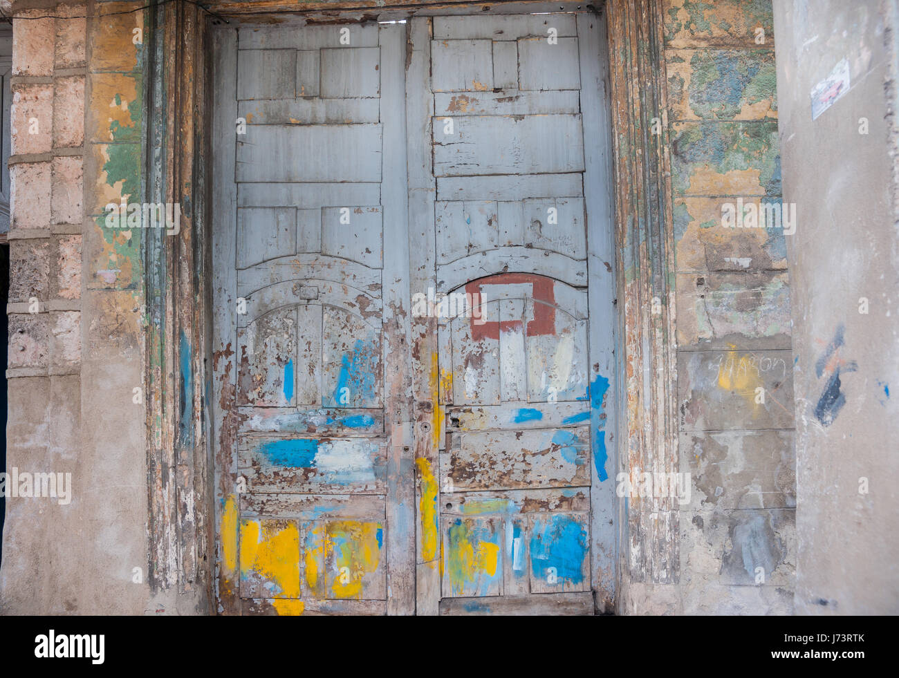 Double closed door seen best of days, daubed in paint, cracked, peeling  weathered and uncared, for in need of repairs - Stock Image