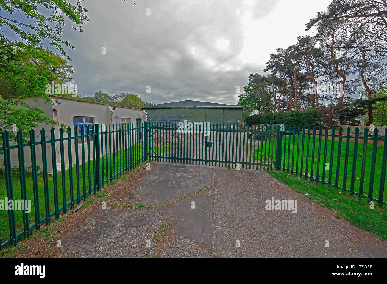 Entrance gates to old hangar type store out in the country. Showing the boundary fence with reception office adjacent Stock Photo