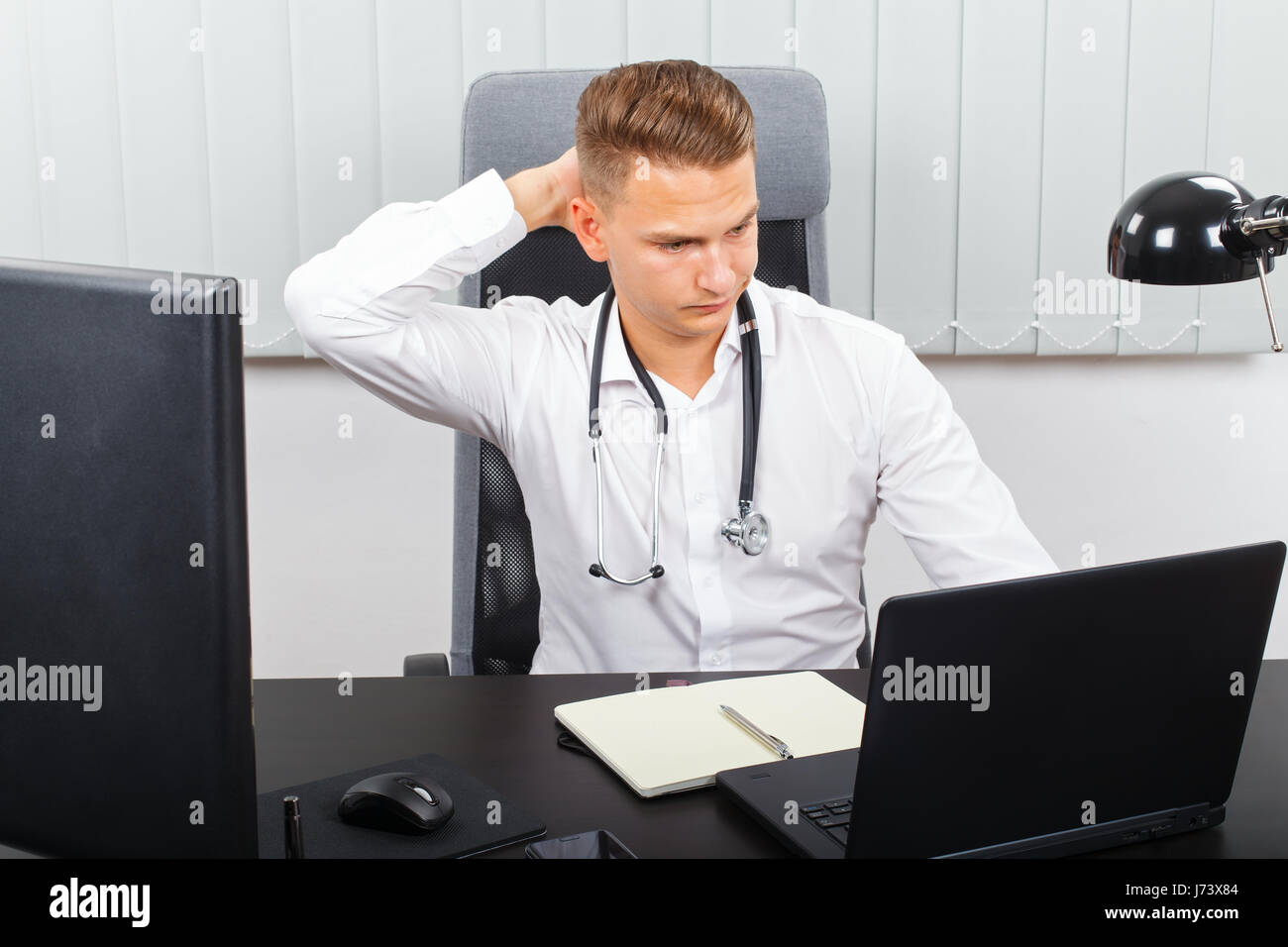 Photo of a stressful young male doctor in his medical office - Stock Image