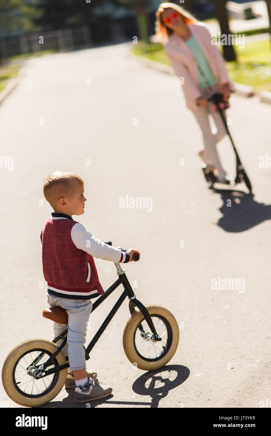 Woman with son on scooters - Stock Image