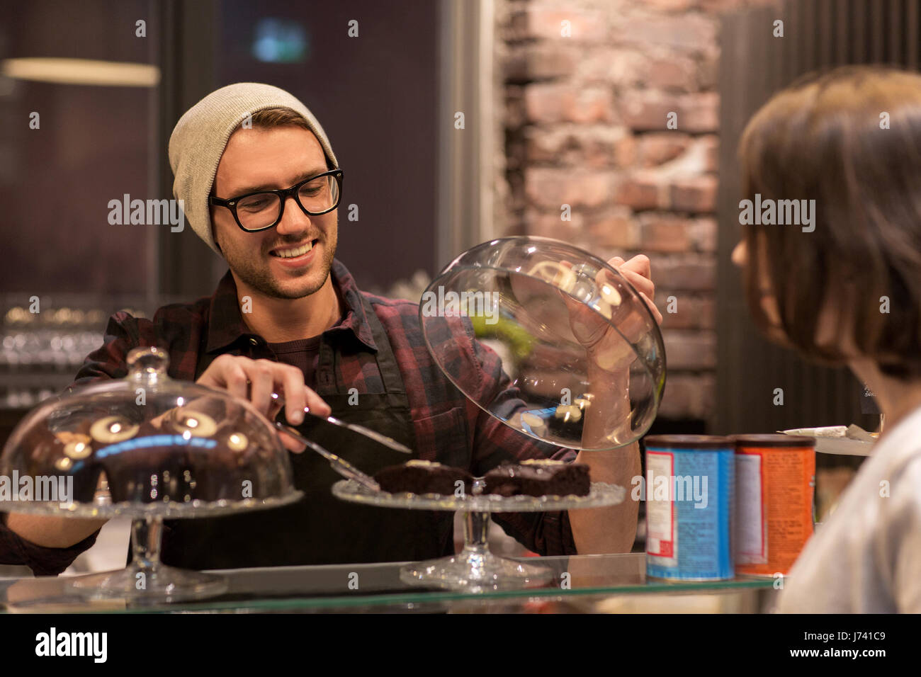 man or barman with cakes serving customer at cafe - Stock Image