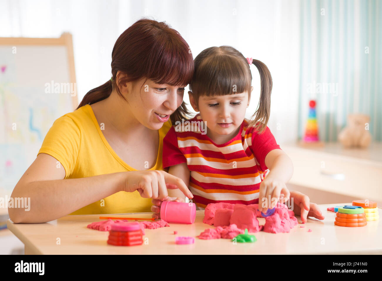 Child and therapist playing with toy the sand. Psychologist works, sand therapy. - Stock Image
