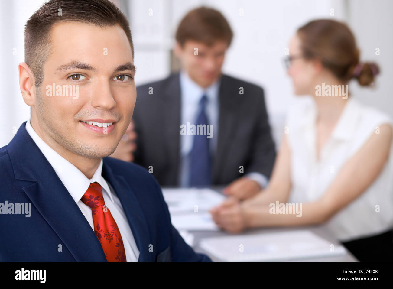 Portrait of cheerful smiling business man  against a group of business people at a meeting. - Stock Image