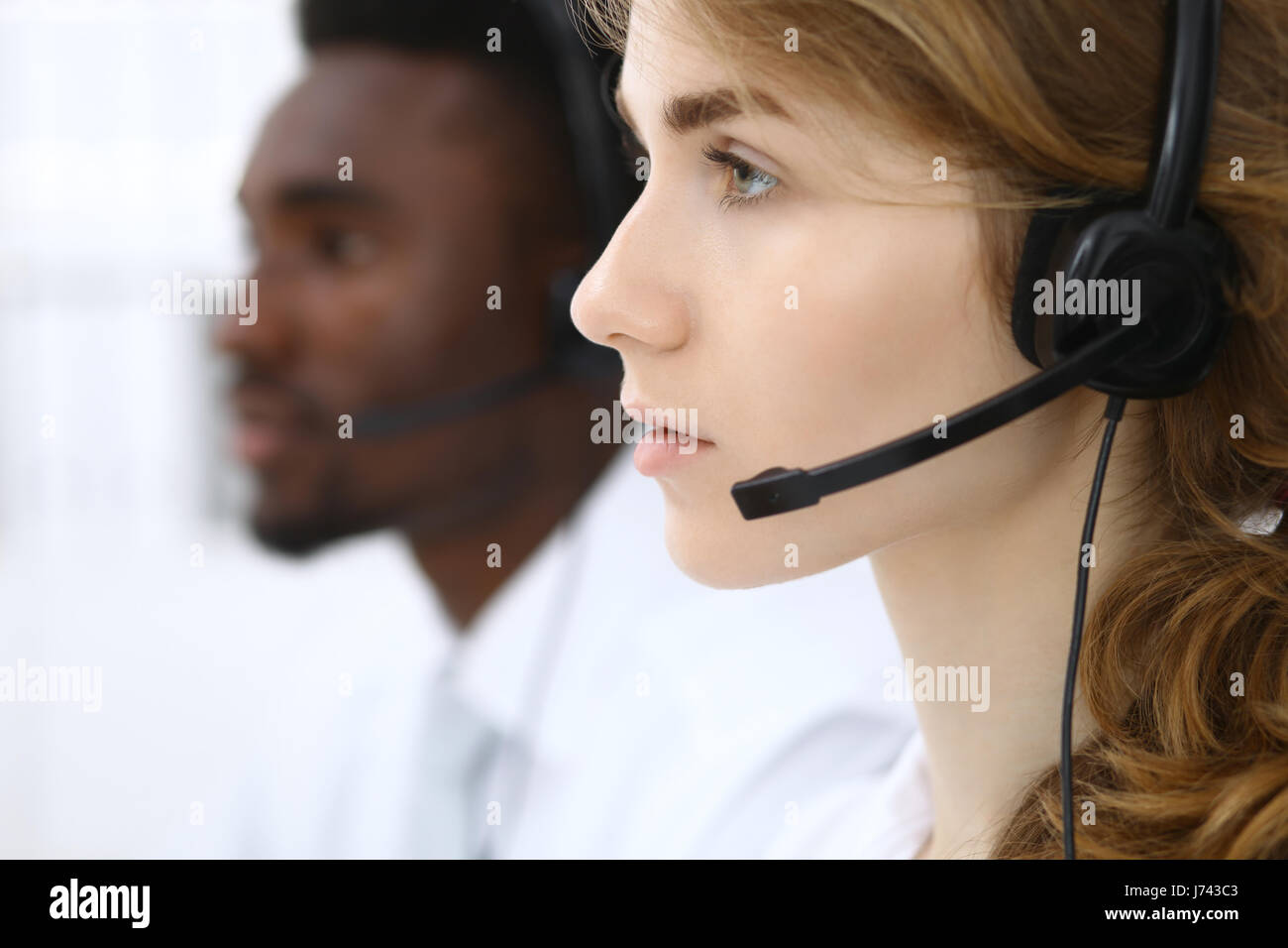 Call center operator.Young beautiful business woman in headset.  - Stock Image