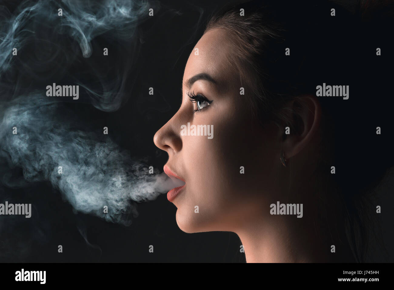The face of vaping young woman at black studio - Stock Image
