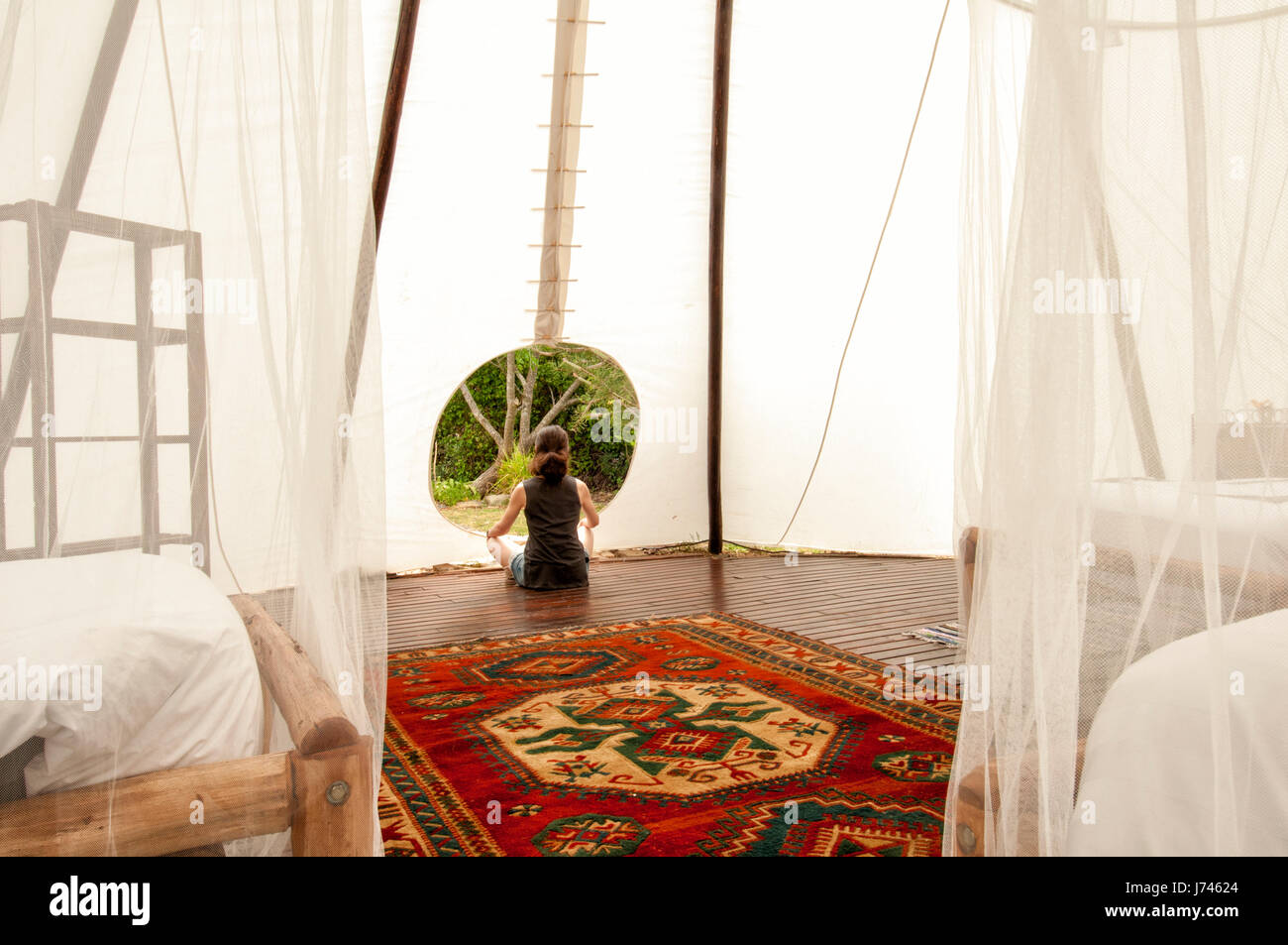 woman meditating at the entrance to a large tipi, glamping. - Stock Image