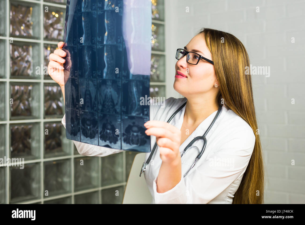 Portrait of intellectual woman healthcare personnel with white labcoat, looking at full body x-ray radiographic - Stock Image