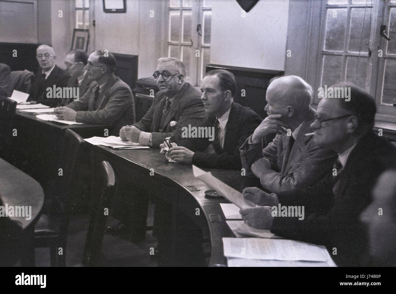 1950s, picture showst male councillors wearing jacket and ties with minutes attending a district council meeting. - Stock Image