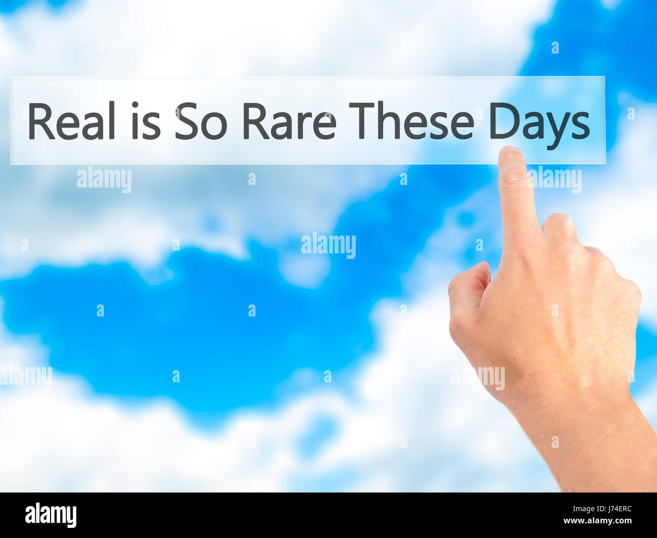 Real is So Rare These Days - Hand pressing a button on blurred background concept . Business, technology, internet - Stock Image