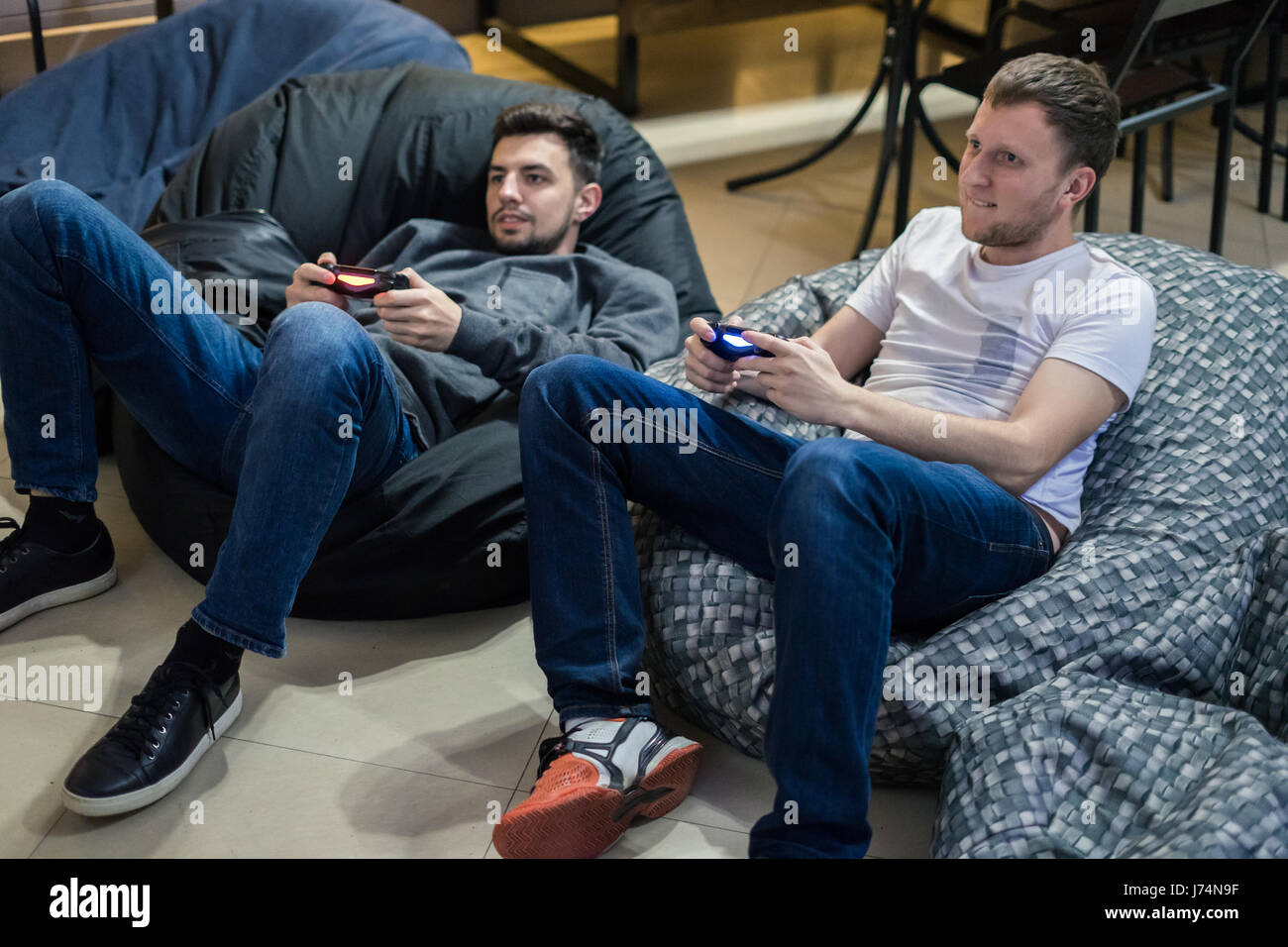 happy couple friends playing video games with joystick sitting on Bean bag chair - Stock Image
