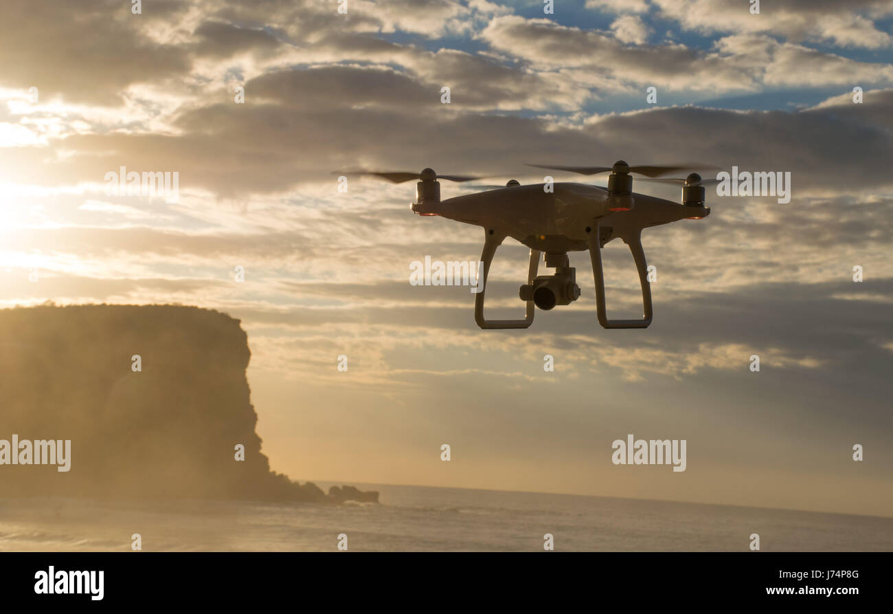 A drone hovers over the ocean as the sun rises - Stock Image
