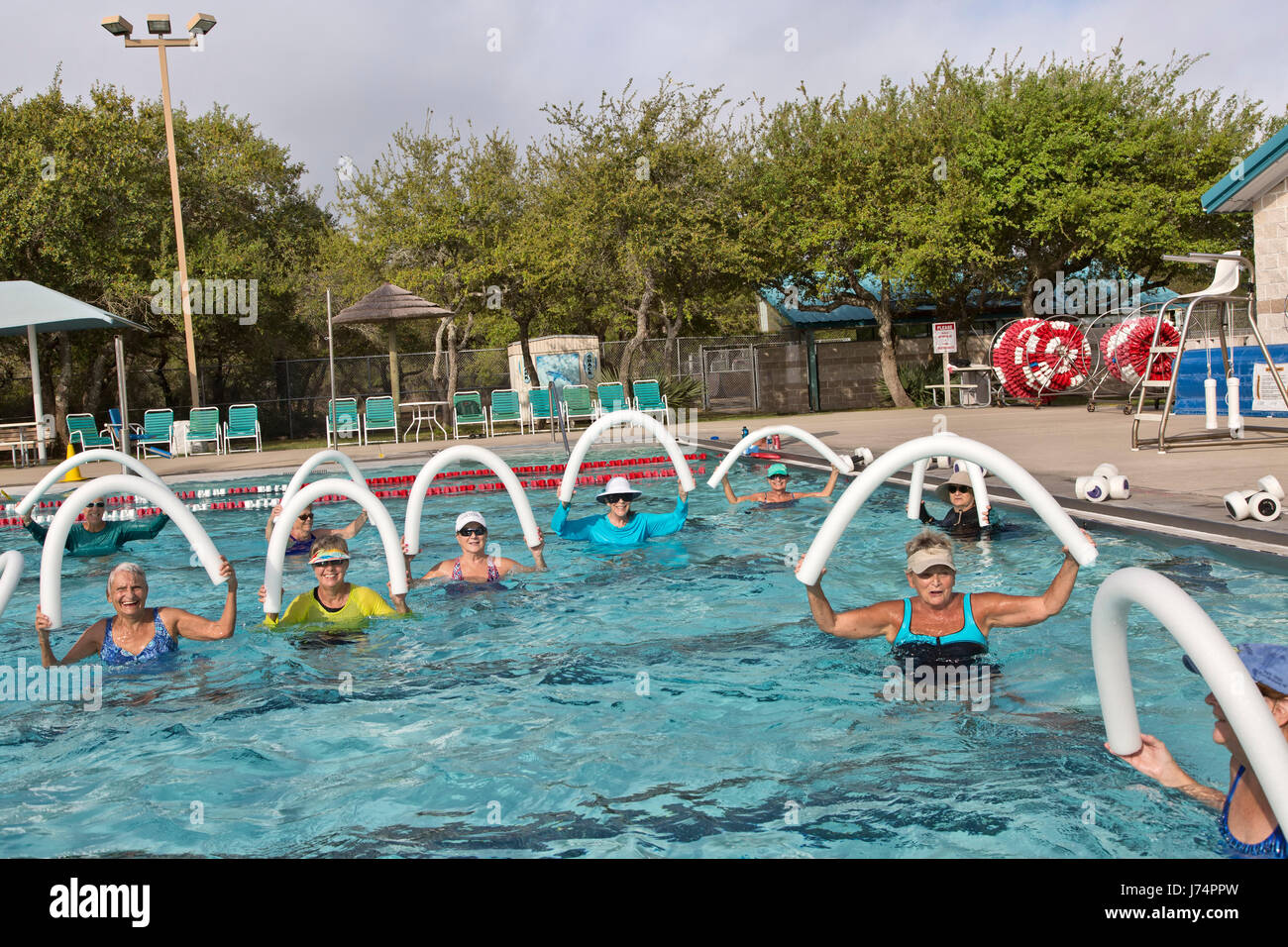 Group of  smiling happy senior women attending Water Aerobics class, using styrofoam  'water noodles', outdoor - Stock Image