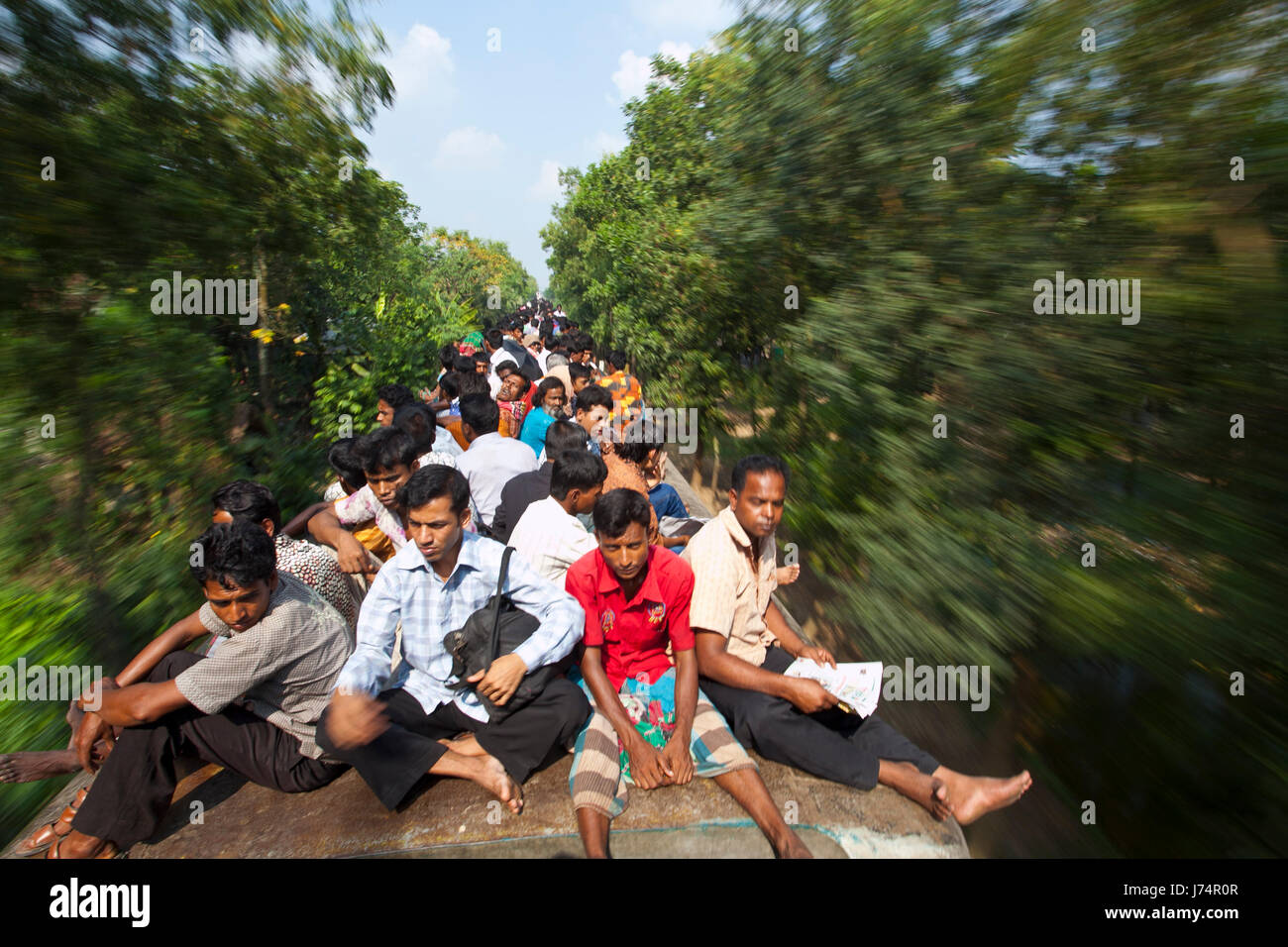 Thousands of Eid vacationers ride on top of train to reach their villages. Gazipur, Bangladesh - Stock Image