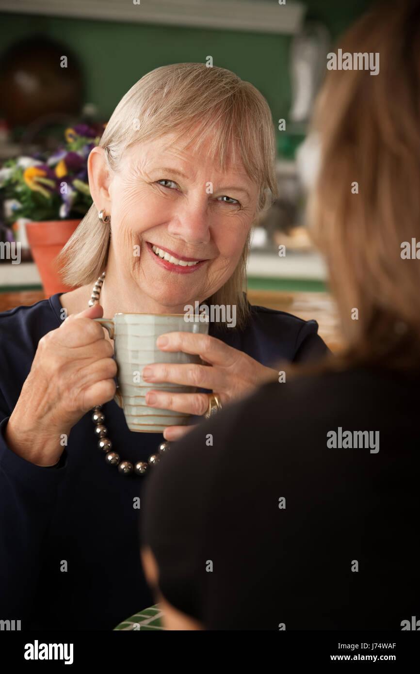 woman talk speaking speaks spoken speak talking chat nattering kitchen cuisine Stock Photo