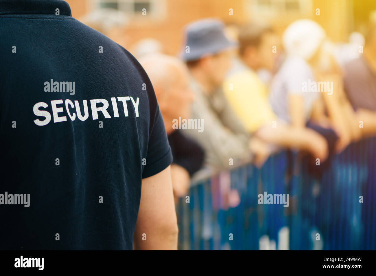 Member of security guard team working on public event, unrecognizable male person from behind - Stock Image