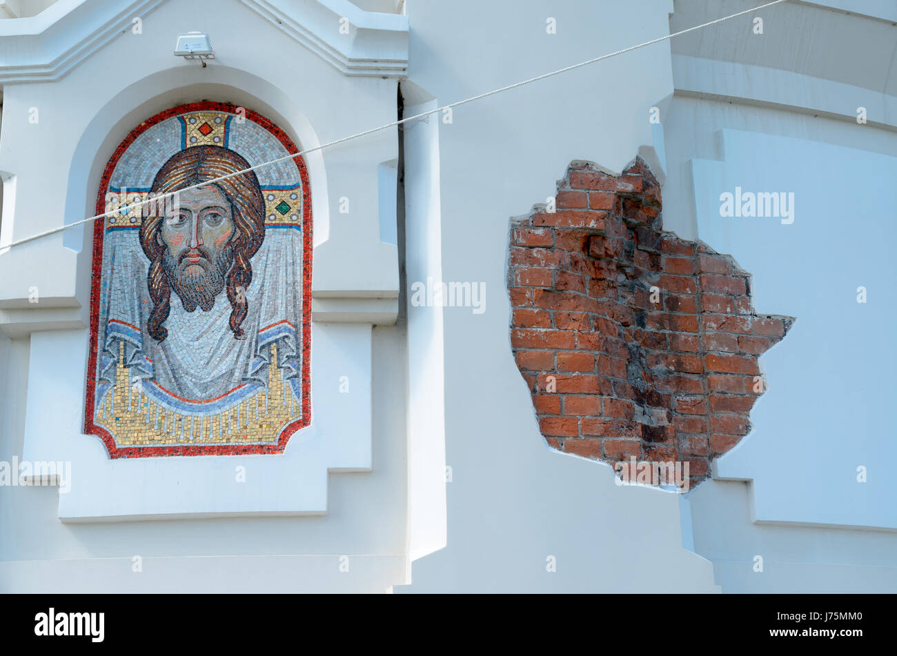 The image of Christ on the wall next to the bare brick. - Stock Image
