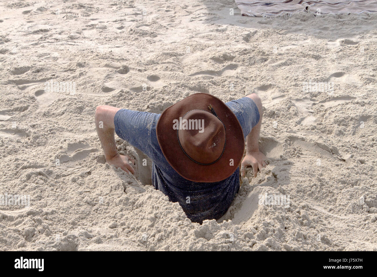 A young man attempts to dig himself out of a hole in the sand that he's gotten himself into on a beach one sunny Stock Photo