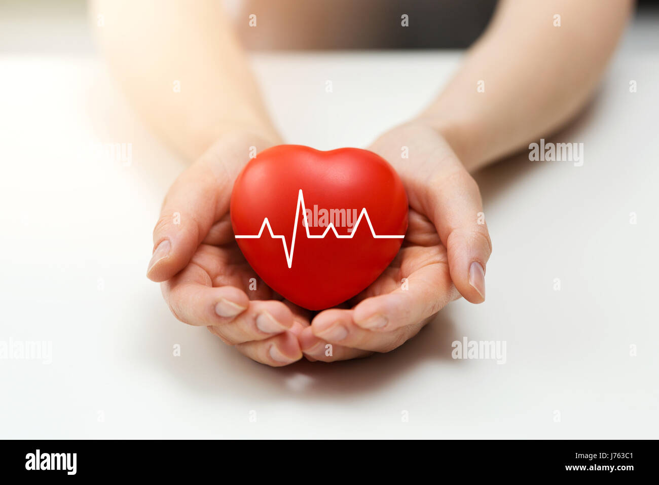 cardiology or health insurance concept - red heart in hands - Stock Image