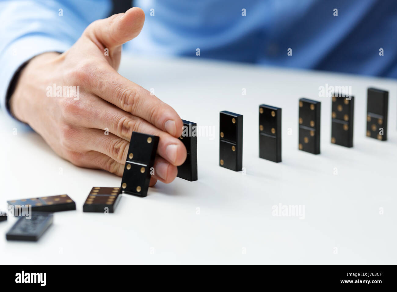 businessman stopping domino effect - business problem solving concept - Stock Image