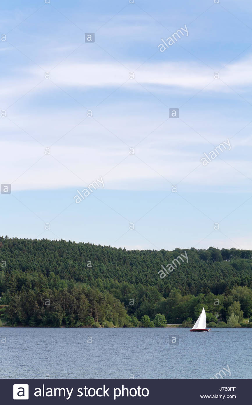 sailing boat sailboat firmament sky salt water sea ocean water forest spare - Stock Image