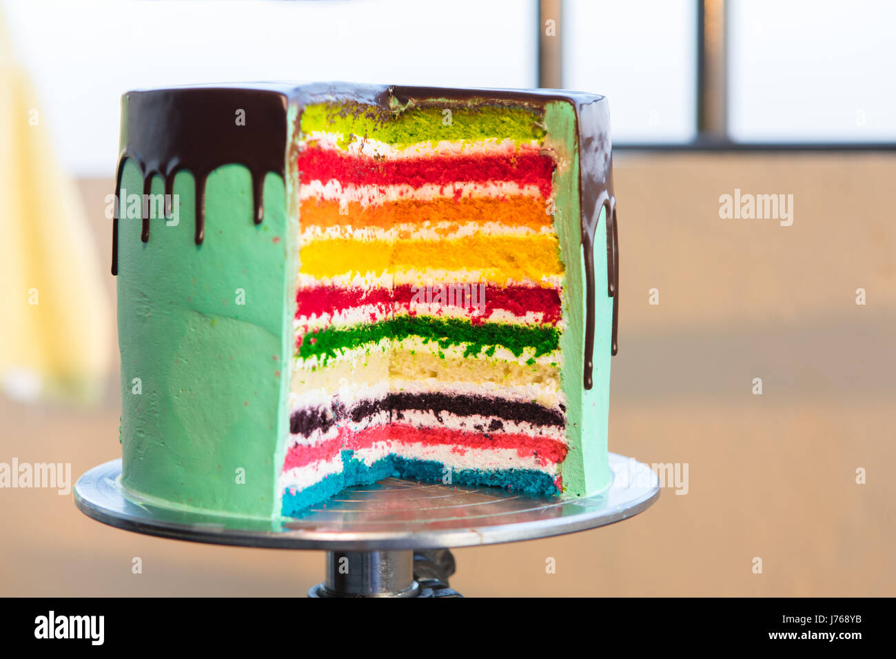 Colorful Rainbow Cake on a stand - Stock Image