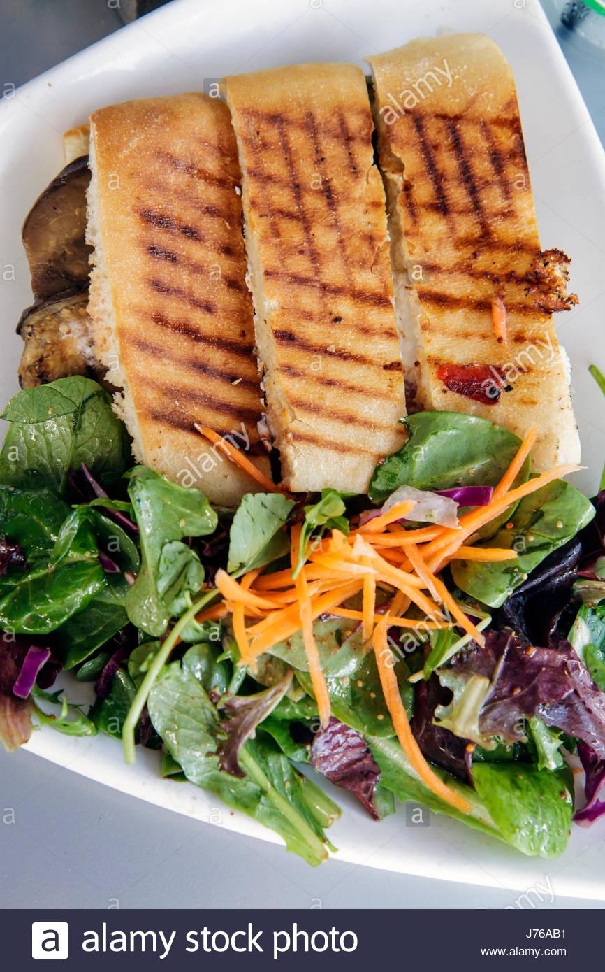 Miami Beach Florida Lincoln Road pedestrian mall alfresco dining restaurant panini sandwich salad plates The Cafe - Stock Image