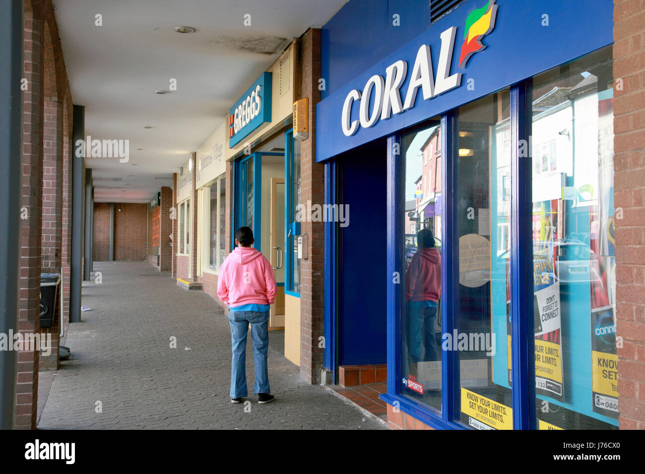Coral Betting shop and Greggs Bakery next to each other on the high street in Market Drayton, Shropshire - Stock Image