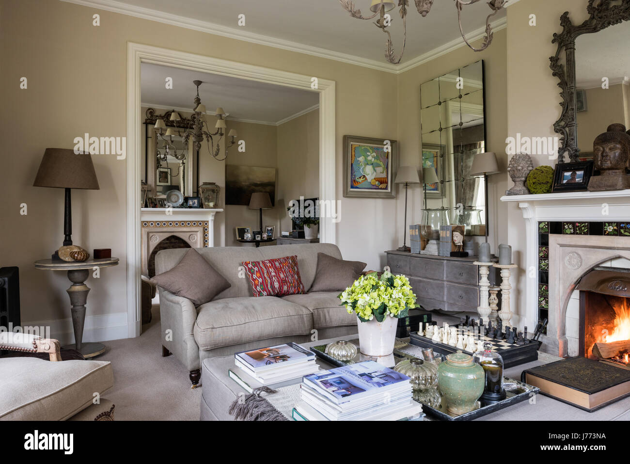 Drawing room with ottoman, chandelier and three-seater linen sofa all from Bardoe & Appel. The walls are painted - Stock Image