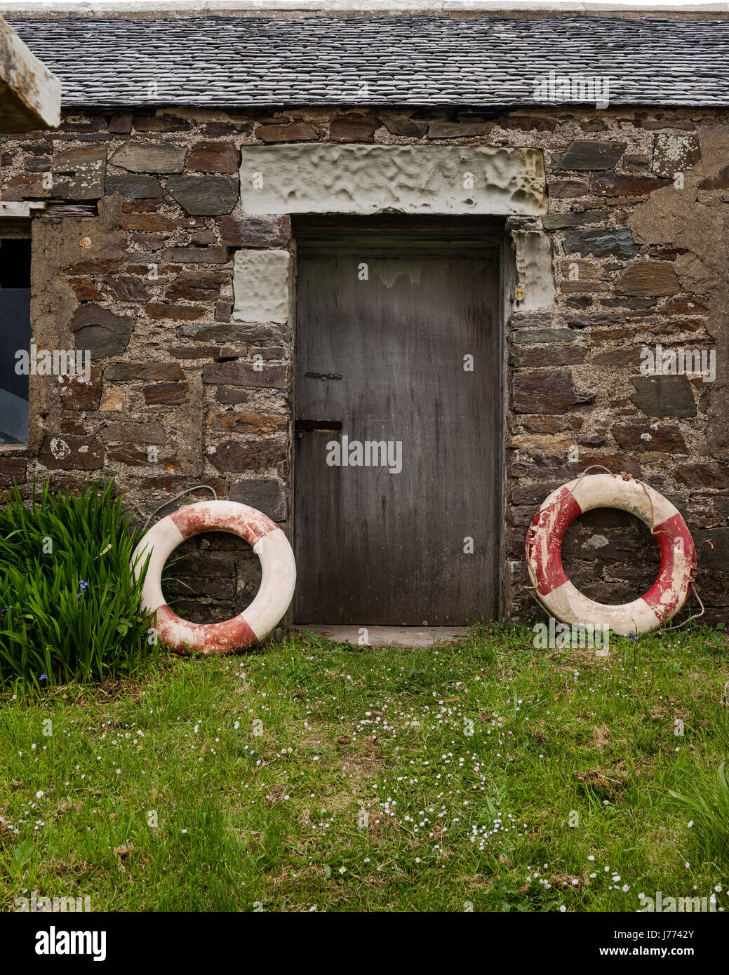 Lifebelts at doorway to stone cottage on Kintyre, Argyll and Bute - Stock Image